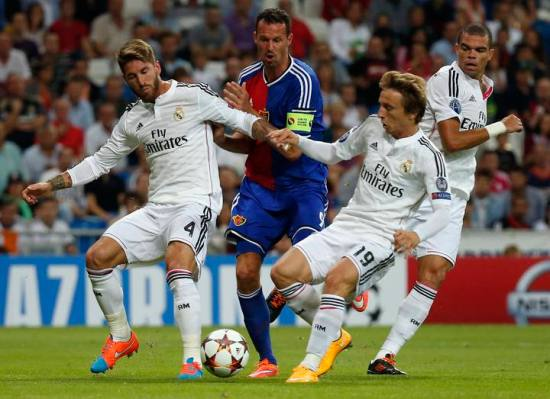 Basel's Streller challenges for the ball with Real Madrid's Ramos, Pepe and Modric during their Champions League soccer match in Madrid